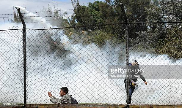 Engulfed by a cloud of tear gas shot by riot police a masked student throws a tear gas grenade back during a demonstration on October 22 2008 at the...