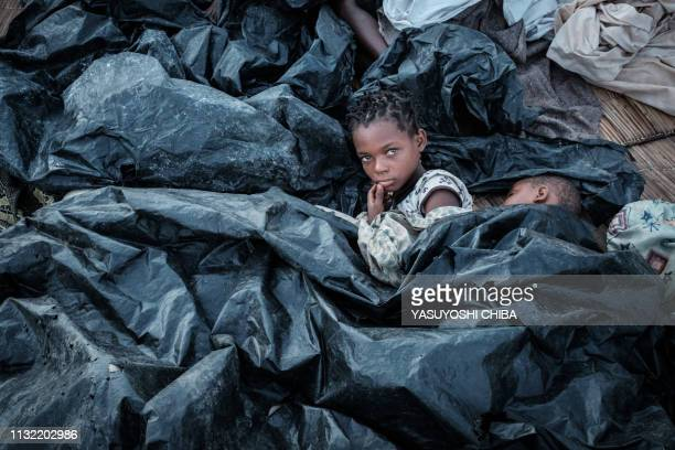 TOPSHOT Enia Joaquin Luis wakes up beside her sister Luisa under plastic sheets for protect themselves from rain as they stay in shelter at the...