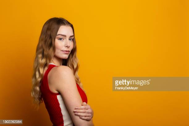 enigmatic and confident attractive blonde young woman against yellow background with copy space, dressed in red dress - person in education stock pictures, royalty-free photos & images