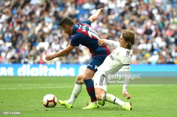 Enis Bardhi of Levante is tackled by Luka Modric of Real Madrid during the La Liga match between Real Madrid CF and Levante UD at Estadio Santiago...