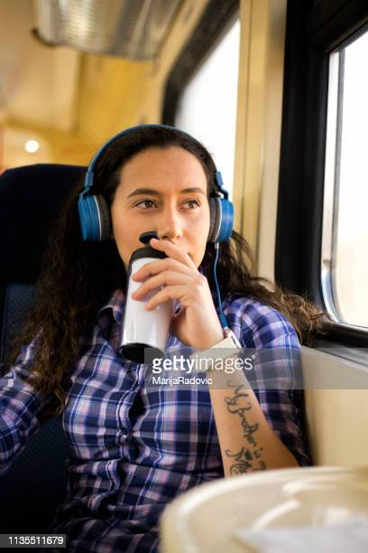 enjoy traveling by train. young woman listening music on headphones and drink coffee - coffee drink stock pictures, royalty-free photos & images