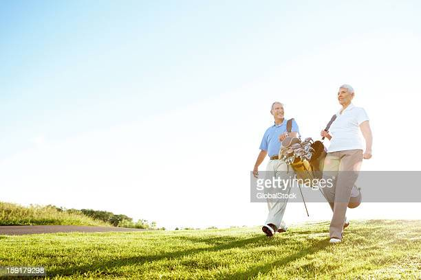 enjoying a bit of leisurely exercise - golfer stock pictures, royalty-free photos & images