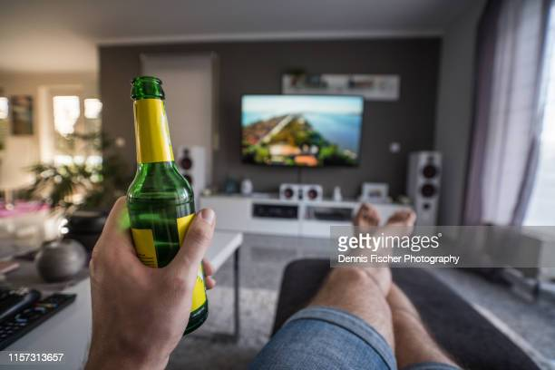 enjoying a drink while watching television - image foto e immagini stock