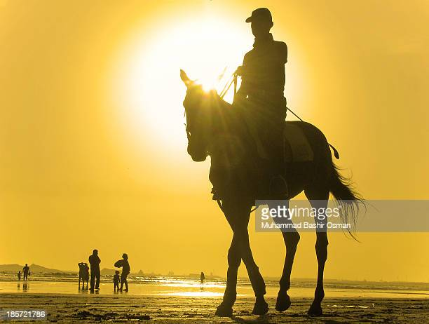 Enjoying a fun ride, while practicing polo, the player is doing the activities at the famous Clifton Beach of Karachi -one of the famous picnic &...