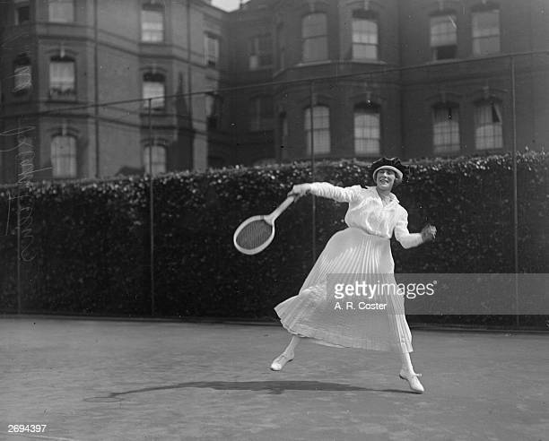 Enjoying a game of tennis at Queen's Club, Madame Reyntiens. Her outfit consists of a large hat, long sleeves and a long pleated skirt.