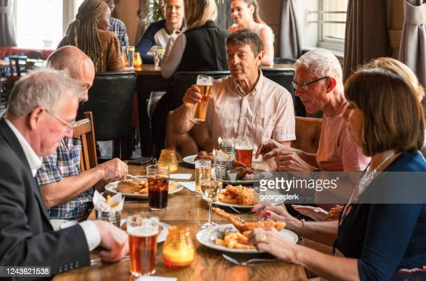 enjoying a pub lunch together - pub stock pictures, royalty-free photos & images