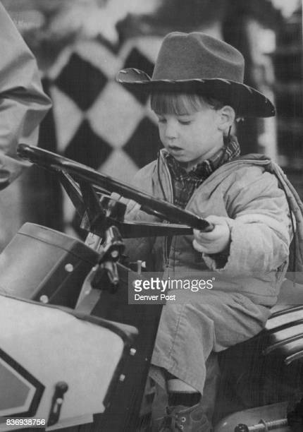Enjoying A Ride At The Stock Show Andrew Collins 2yearold from Cheyenne Wyo enjoys a ride in fantasy on an Allis Chalmers Simplicity tractor at the...