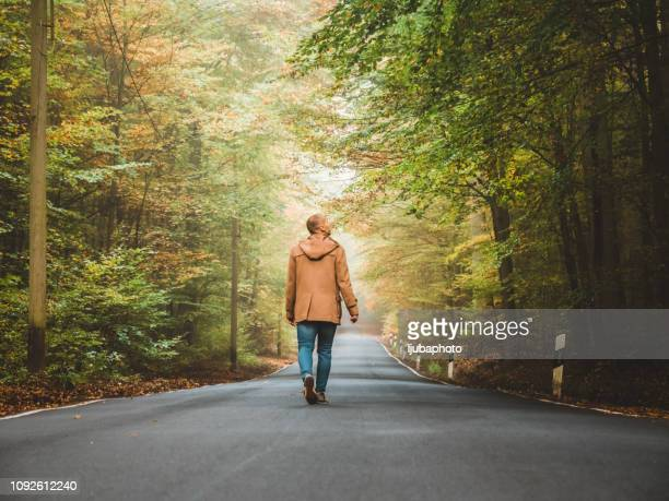 enjoying a solitary walk - leaving stock pictures, royalty-free photos & images