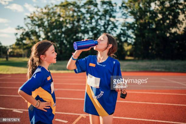 enjoying a water break at athletics club - drinking water stock pictures, royalty-free photos & images