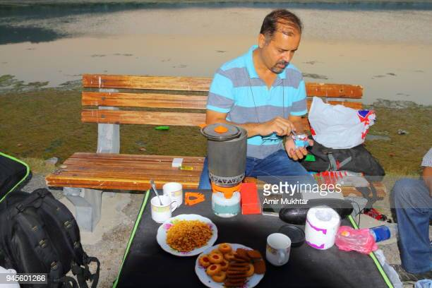 enjoying and preparing tea on lake - amir mukhtar stock photos and pictures