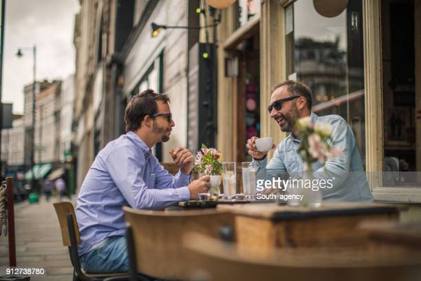 enjoying breakfast break in coffee shop - mid adult men stock pictures, royalty-free photos & images