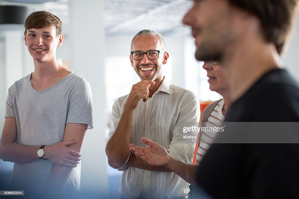 Enjoying discussions in a stand up meeting : Stock-Foto