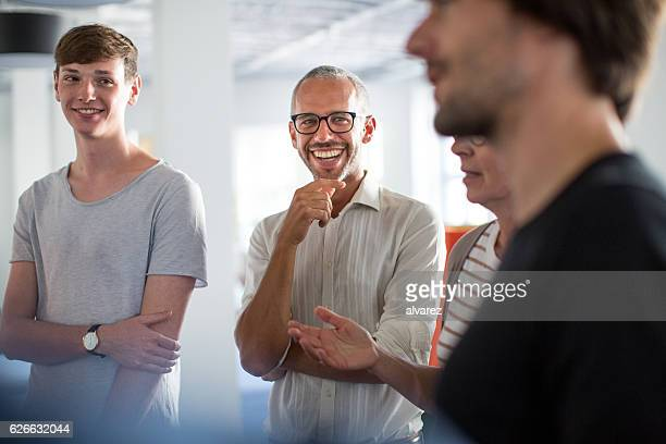 enjoying discussions in a stand up meeting - casual clothing stock pictures, royalty-free photos & images