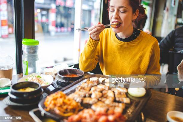 enjoying her travel in korean restaurant, tasting barbecue - korean culture stock pictures, royalty-free photos & images