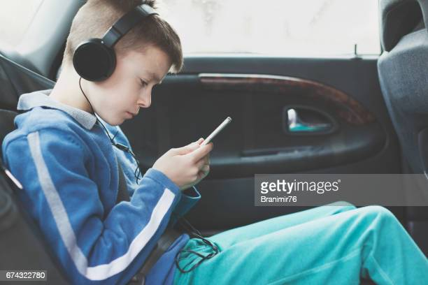 Enjoying in a car driving with phone and headphones