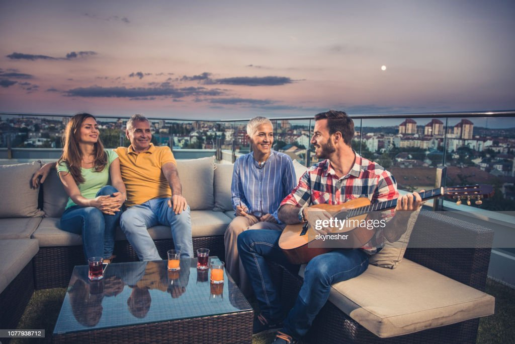 Enjoying in a sound of acoustic guitar on a penthouse terrace! : Stock Photo