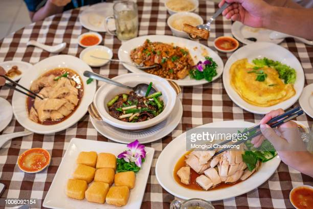 enjoying lunch with friends. top view of group of people having lunch together at chinese restaurant in singapore while happy to eating hainanese food. - hainan island stock pictures, royalty-free photos & images