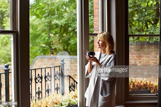 enjoying morning calm and coffee - erker stockfoto's en -beelden