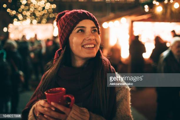 enjoying mulled wine at christmas market - christmas market stock pictures, royalty-free photos & images