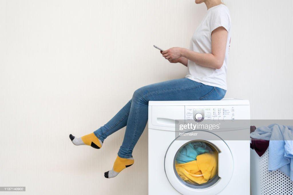Genießen Sie die einfache Wäsche. Profilseitige Ansicht der Dame, die oben auf der weißen Waschmaschine sitzt und die Smartphone-App im hellen hellen, flachen Innenraum betrachtet. : Stock-Foto