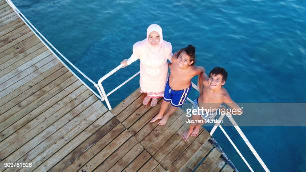 enjoying on the beach, aerial view - muslim woman beach stock photos and pictures