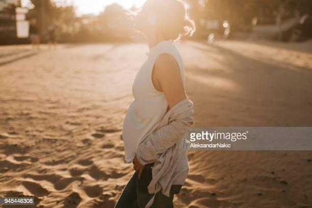 genieten van zwangerschap - handen op de buik stockfoto's en -beelden