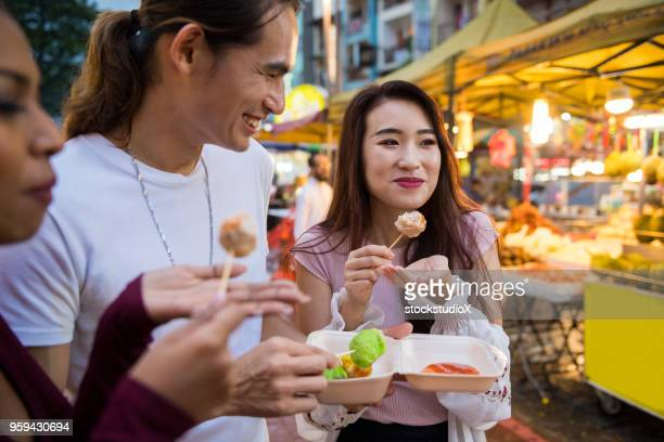 enjoying street food at a local night market - malaysian culture stock pictures, royalty-free photos & images