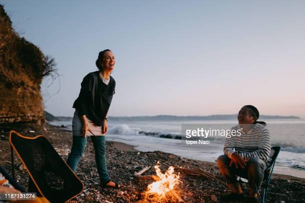enjoying sunset campfire at beach, tokyo bay - 自然 ストックフォトと画像