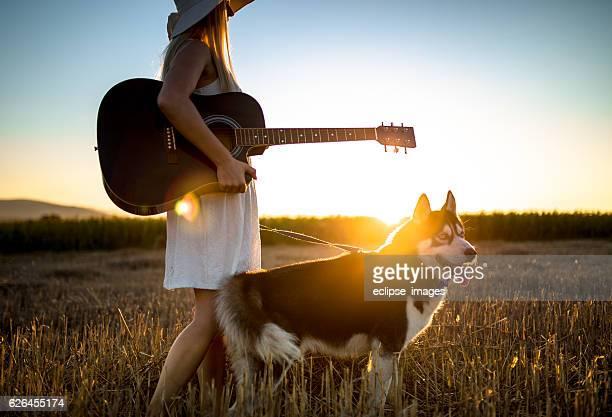 Enjoying sunset with dog and guitar