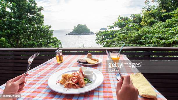 enjoying tasty breakfast on the sea view terrace - snag tree stock pictures, royalty-free photos & images