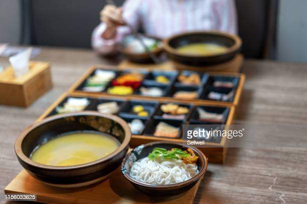 enjoying the crossing bridge noodles in yunnan - noodles stock pictures, royalty-free photos & images