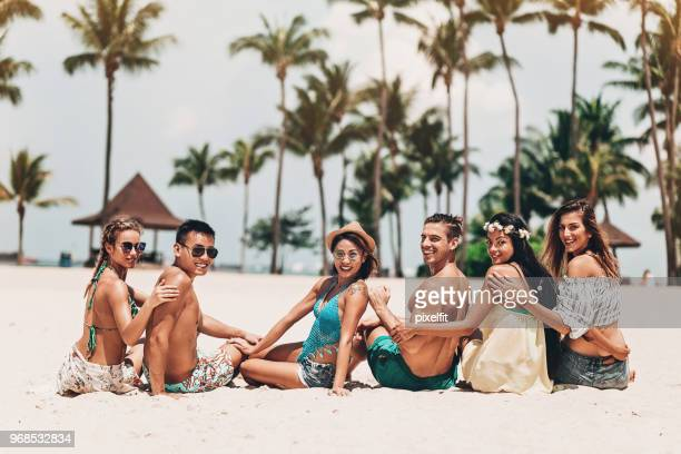 enjoying the sand and the ocean - medium group of people stock pictures, royalty-free photos & images