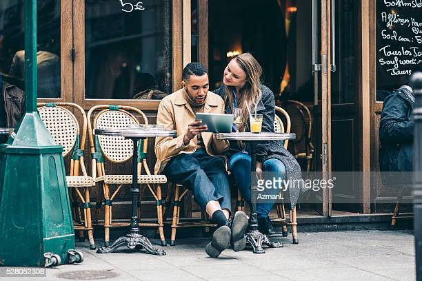 enjoying their time together - french cafe stock photos and pictures