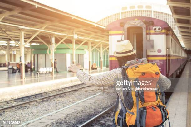 Enjoying travel. Young traveler walking with backpack and classic train at railway platform. alone travel and summer concept. vintage filter.
