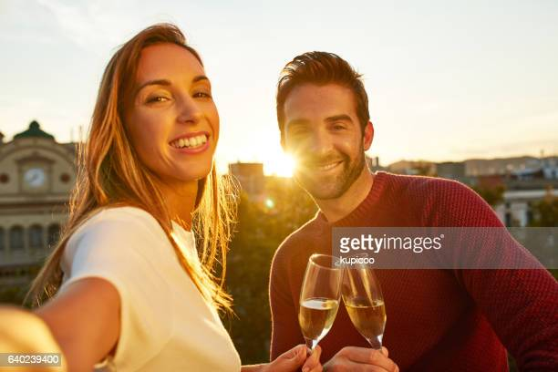 Enjoying wine and a city sunset