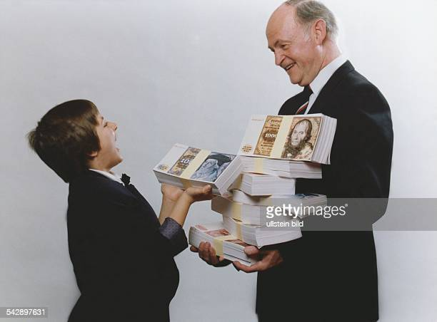 Enkel und Großvater stehen sich gegenüber Der Junge hält ein dickes Geldscheinbündel mit Hundertmarkscheinen in den Händen Der Mann hat mehrere...