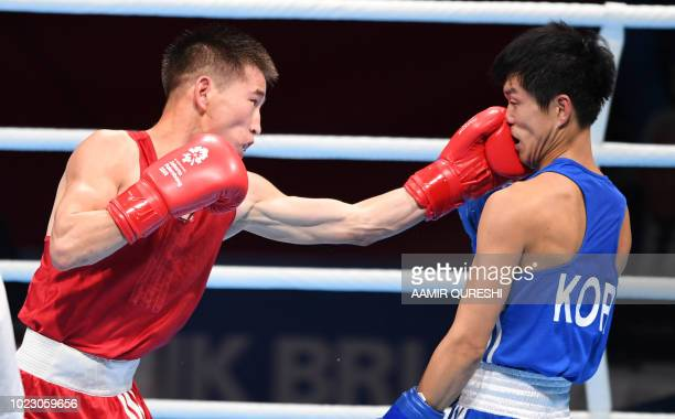 Enkhmandakh Kharkhuu of Mongolia connects with a lefthand punch against Shin Jonghun of South Korea during their men's light fly 49kg boxing round of...