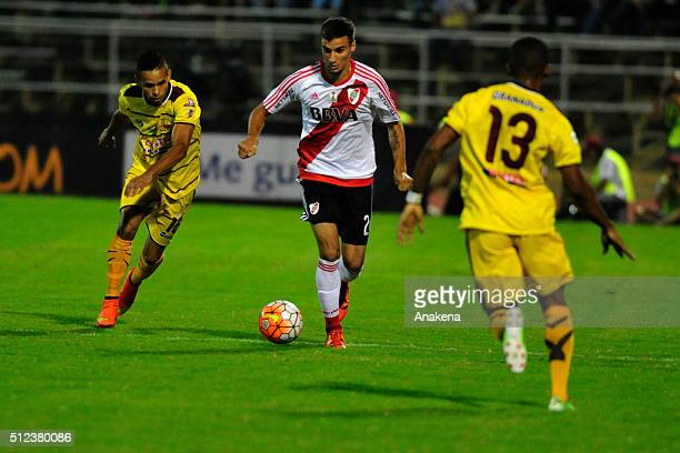 Enmanuel Manmana of River Plate struggles for the ball with Angel Nieves of Trujillanos during a group stage match between Trujillanos and River...