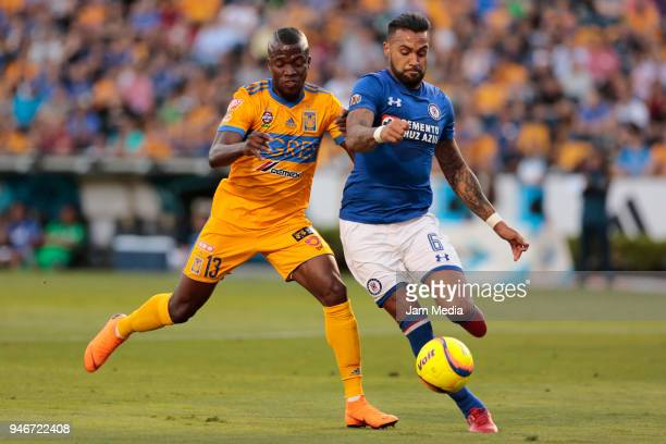 Enner Valencia of Tigres and Julian Velazquez of Cruz Azul fight for the ball during the 15th round match between Tigres UANL and Cruz Azul as part...