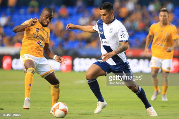 Enner Valencia of Tigres fights for the ball with Anderson Santamaria of Puebla during a match between Tigres UANL and Puebla as part of Round of...