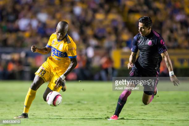 Enner Valencia of Tigres fights for the ball with Carlos Cisneros of Chivas during the 12th round match between Tigres UANL and Chivas as part of the...