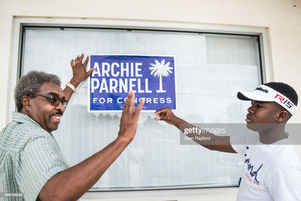 Ennis Bryant (L) and his grandson DeShawn Vereen hang up a campaign sign for Democratic congressional candidate Archie Parnell June 19, 2017 in Bishopville, South Carolina. Voters will choose between Parnell and Republican candidate Ralph Norman tomorrow in a special election for South Carolina's 5th Congressional District House seat.