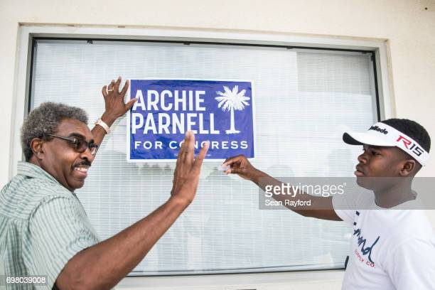 Ennis Bryant and his grandson DeShawn Vereen hang up a campaign sign for Democratic congressional candidate Archie Parnell June 19 2017 in...
