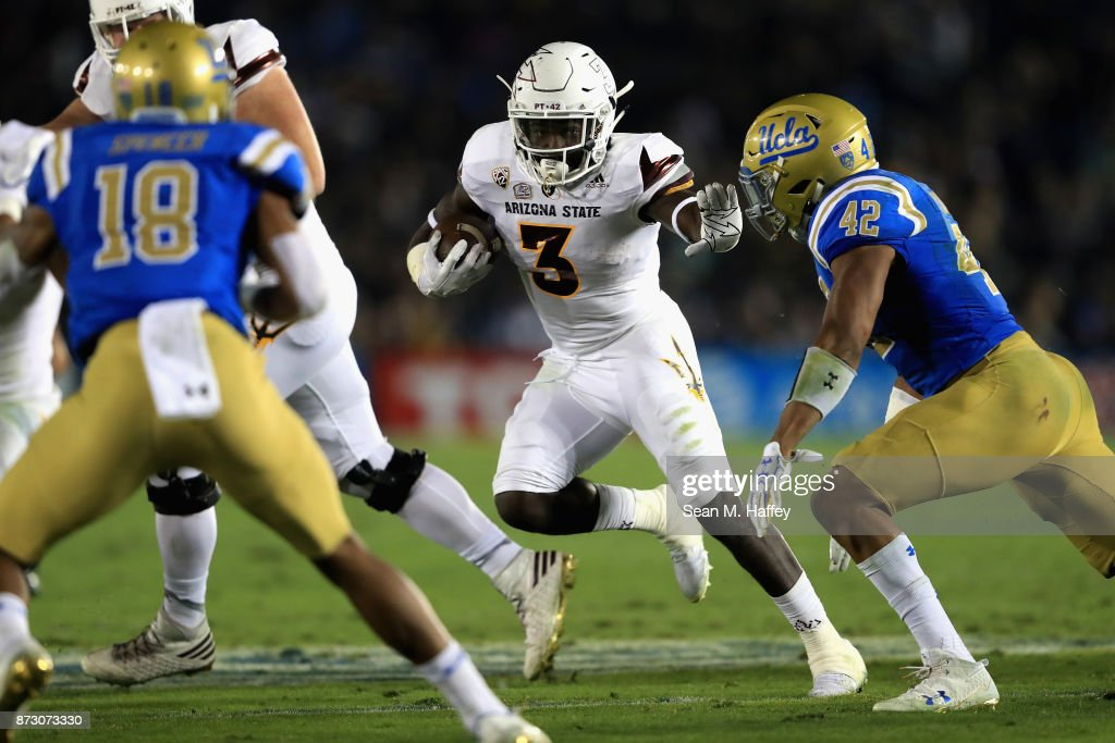 Eno Benjamin #3 of the Arizona State Sun Devils runs past Kenny Young #42 and Octavius Spencer #18 of the UCLA Bruins during the first half of a game at the Rose Bowl on November 11, 2017 in Pasadena, California.