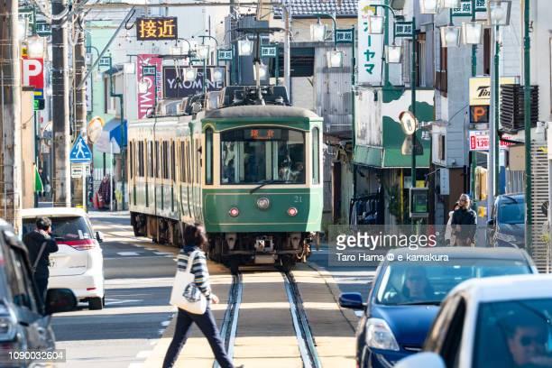 Enoden, Enoshima Electric Railway running in the shopping street in Kamakura in Japan