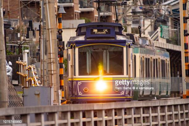 Enoden (Enoshima Electric Railway) running by the sea in Kamakura city in Japan in the morning