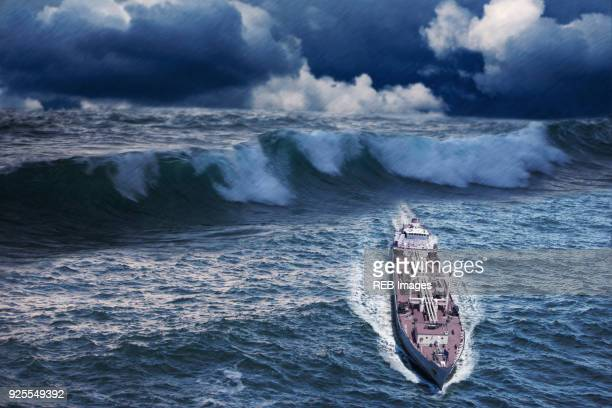 enormous waves behind freighter - slave ship stock photos and pictures
