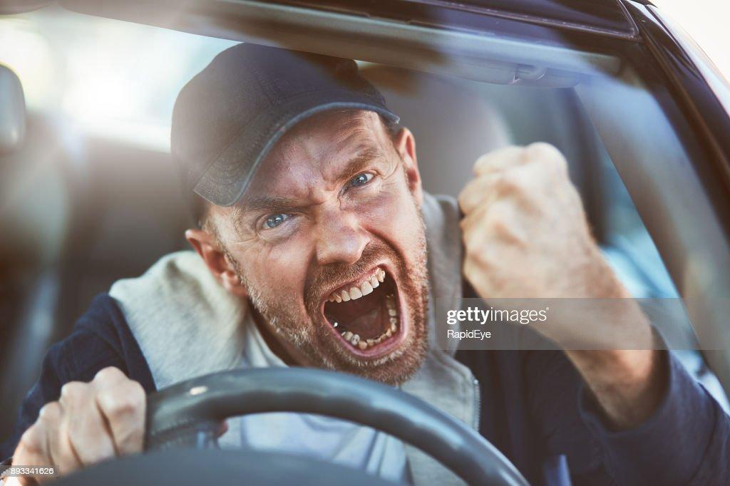 Enraged man shaking fist through windscreen: road rage : Stock Photo