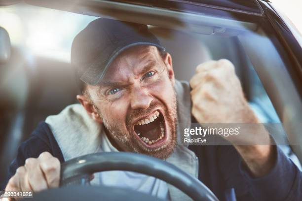 enraged man shaking fist through windscreen: road rage - fury stock pictures, royalty-free photos & images