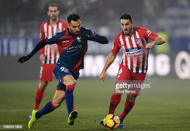 Enric Gallego of SD Huesca battles for possession with Koke of Atletico Madrid during the La Liga match between SD Huesca and Club Atletico de Madrid...